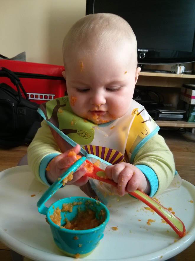 Baby enjoying carrot in Bumbo