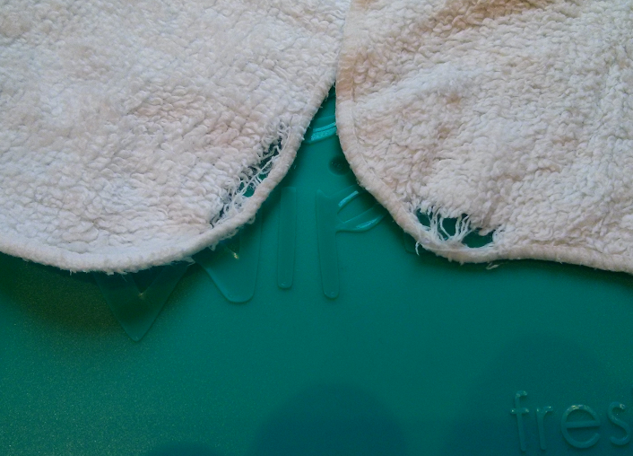 Frayed hems of two wipes.