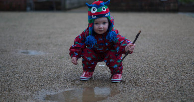 Small child hitting puddle with a stick